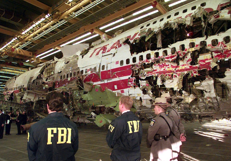 In this Nov. 19, 1997 file photo, FBI agents and New York state police guard the reconstruction of TWA Flight 800 in Calverton, N.Y. Flight 800 exploded and crashed July 17, 1996 while flying from New York to Paris, killing all 230 people aboard. Former investigators on Wednesday, June 19, 2013 called on the National Transportation Safety Board to re-examine the cause, saying new evidence points to the often-discounted theory that a missile strike may have downed the jumbo jet. (AP Photo/Mark Lennihan, File)
