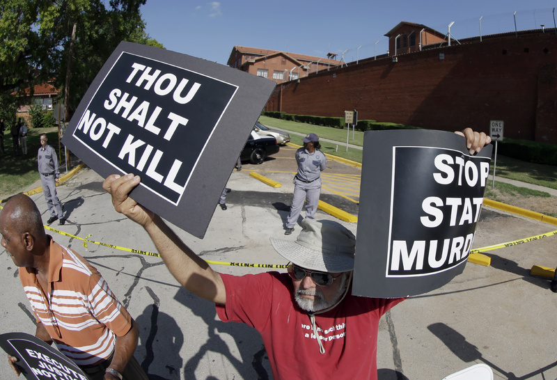 Habi Jawad holds up his signs to protest the execution of Kimberly McCarthy on Wednesday outside the Texas Department of Criminal Justice Huntsville Unit, where the death chamber is located, in Huntsville, Texas.