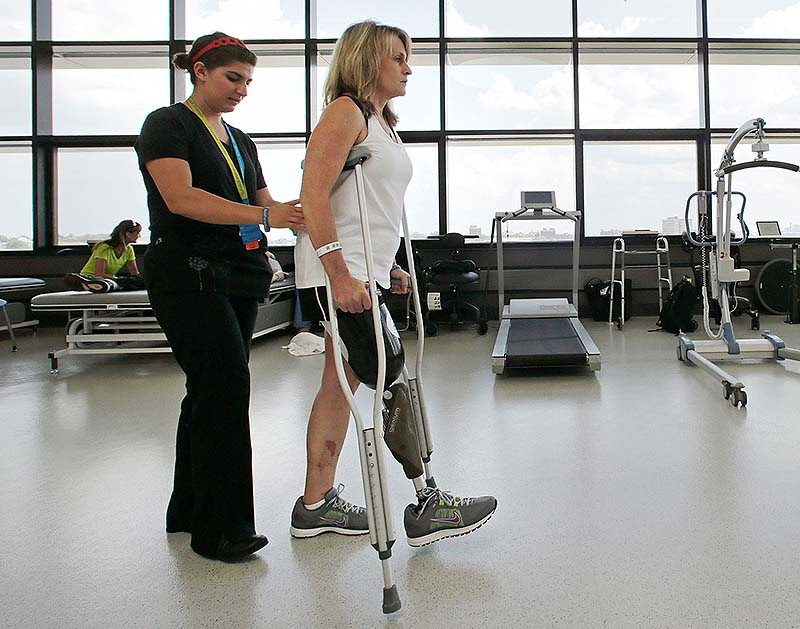 With physical therapist Dara Casparian, left, guiding her strides, Boston Marathon bombing survivor Roseann Sdoia, of Boston, looks forward toward a mirror at the Spaulding Rehabilitation Hospitalin Boston. Sdoia went back to the hospital to learn to walk with her new leg.