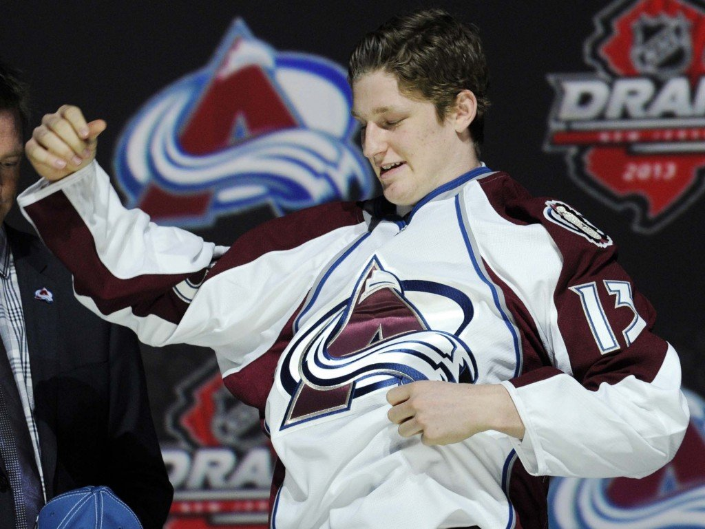 Nathan MacKinnon, a center, pulls on a Colorado Avalanche sweater after being chosen 1st overall in the first round of the NHL draft on Sunday.