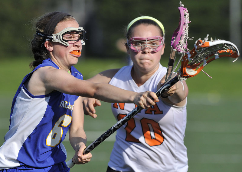 London Bernier, left, of Falmouth attempts to get off a shot Friday while defended by Shelby Peavey of North Yarmouth Academy during their schoolgirl lacrosse regular-season finale. Falmouth won 21-10 and will be at York in the first round of the playoffs. NYA's season came to an end.