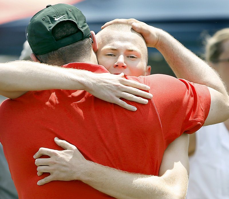 Robert Hall of Scarborough hugs Coach Derek Veilleux after winning a tiring 1,600 state final in 4:25.83.