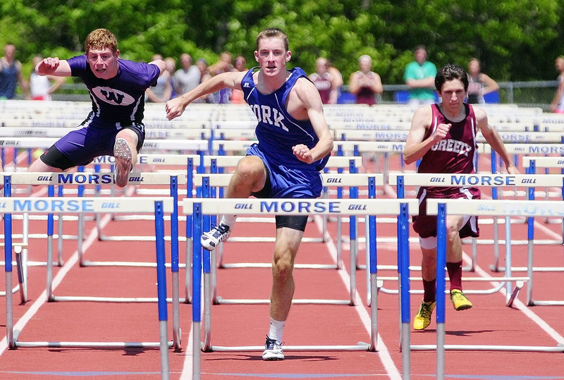 Tom Reid, center, of York captures the 110-meter hurdles in 15.43 seconds, finishing ahead of Jordhan Levine, left, of Waterville, who was second, and Ben Giffard of Greely.