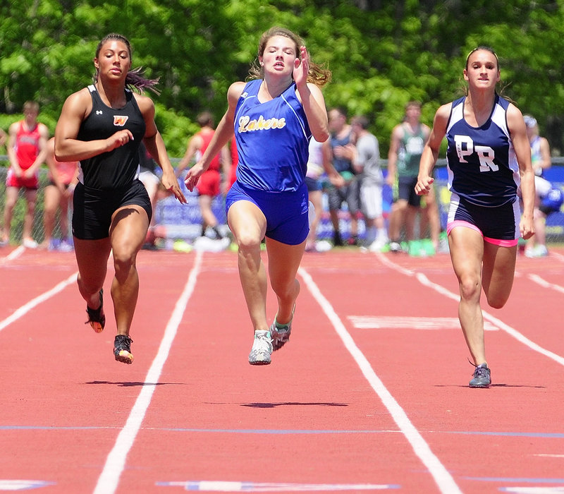Kate Hall, center, of Lake Region sprints to the finish ahead of Alliyah Veilleux, left, of Winslow to capture the 100-meter title in 12.15 seconds, beating the Class B record she set a year ago.