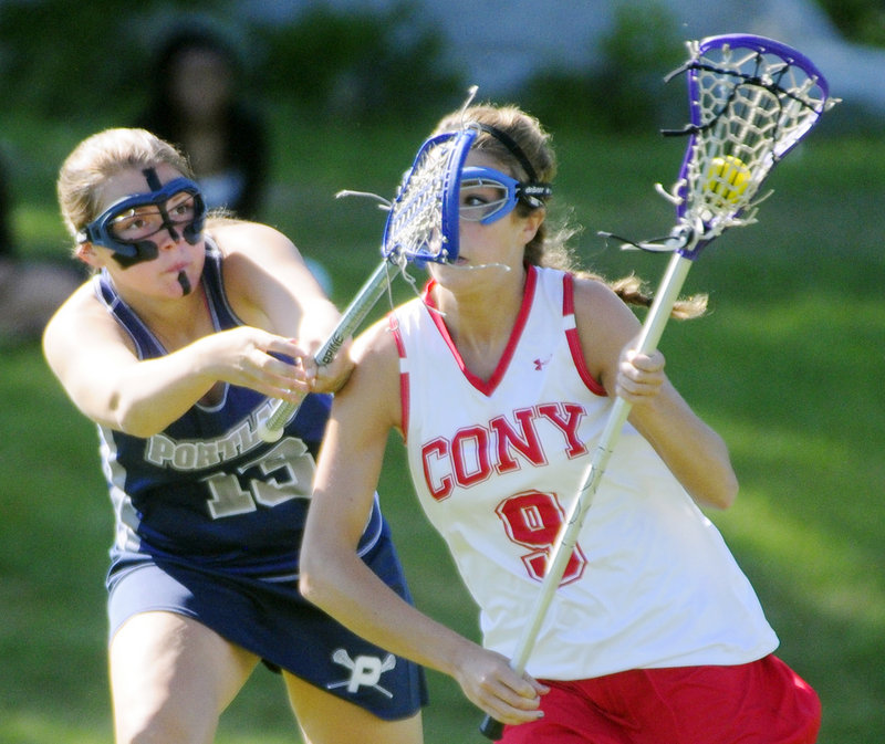 Ashley Frank, left, of Portland tries to stop Cony's Josie Lee as she breaks toward the goal during their Eastern Class A lacrosse semifinal Wednesday in Augusta. Fourth-seeded Cony advanced with a 12-8 victory.
