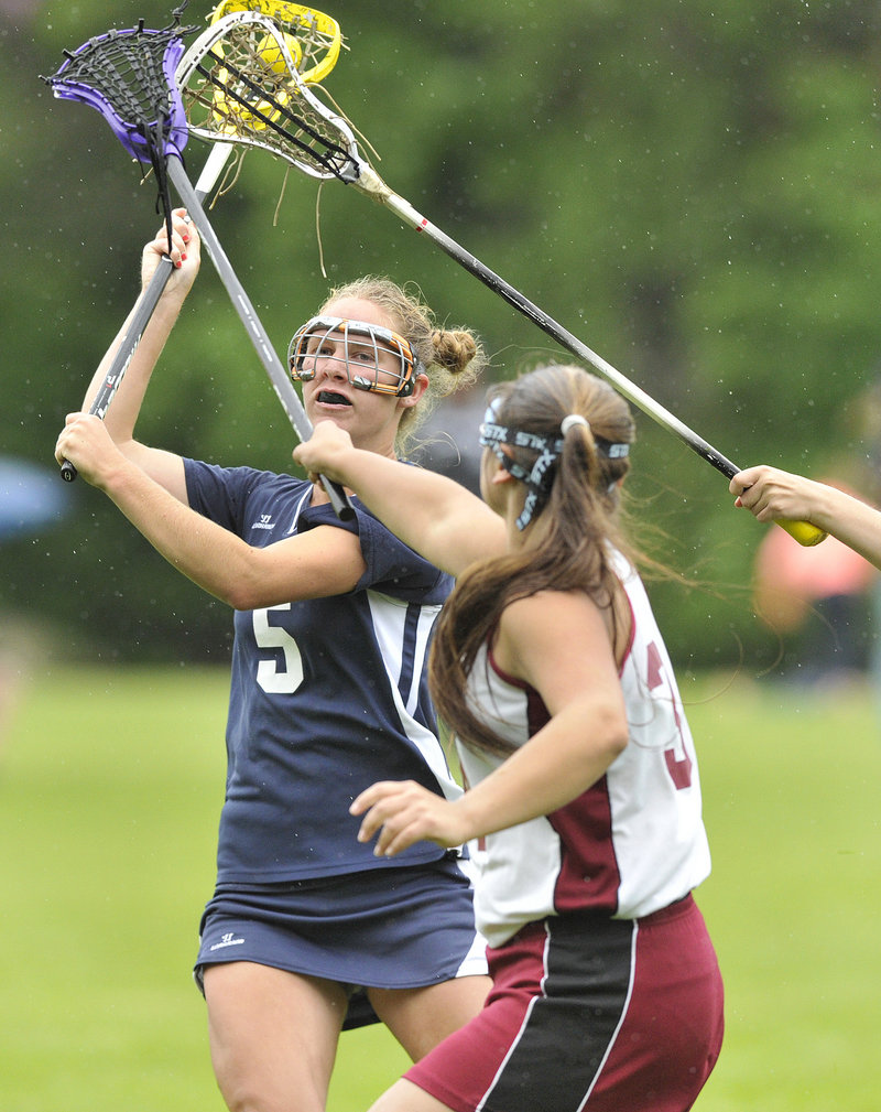 Alex Lucas of Yarmouth, left, gets off a shot Friday while defended by Megan Peacock of Freeport during the Eastern Class B girls' lacrosse semifinal.