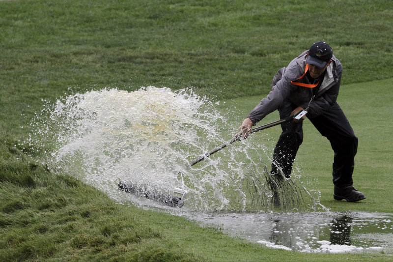 A course worker clears water Monday from the 16th fairway during practice for the U.S. Open golf tournament at Merion Golf Club in Ardmore, Pa.