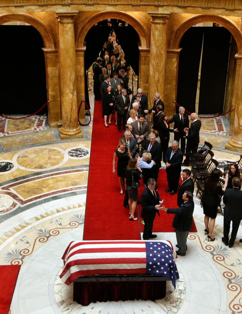 The flag-draped casket of former Massachusetts Gov. Paul Cellucci lies in repose in the Hall of Flags as mourners line up to pay their respect at the Statehouse in Boston on Thursday. Cellucci died Saturday at his home in Hudson from complications of ALS, also known as Lou Gehrig's disease.