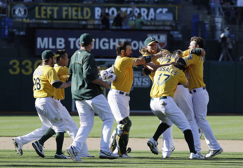 Oakland's Nate Freiman, second from right, is mobbed after hitting a game-winning RBI single off New York Yankees pitcher Mariano Rivera in the 18th inning Thursday at Oakland.