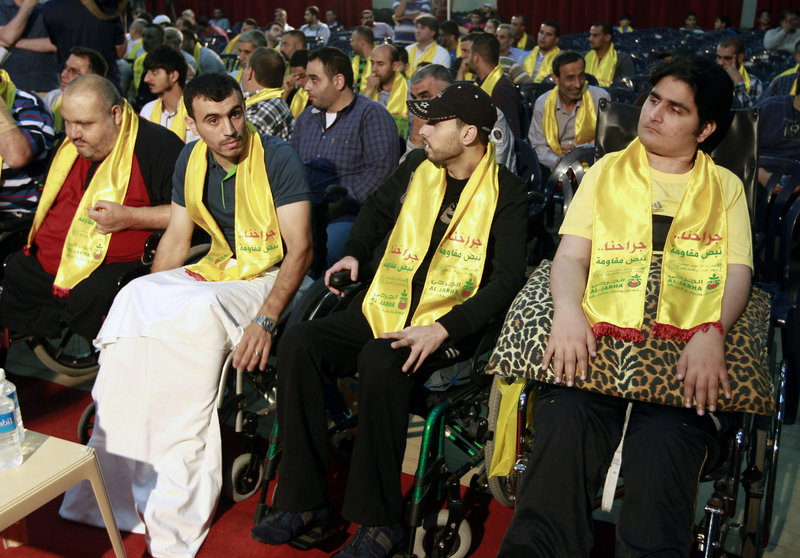 Injured Hezbollah fighters listen to a speech by Hezbollah leader Sheikh Hassan Nasrallah on a screen via a video link during a rally to mark
