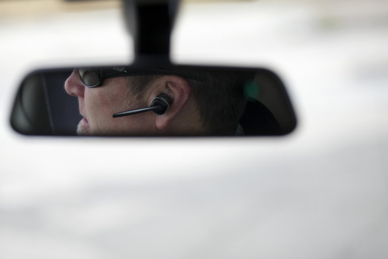 A motorist uses a hands-free device to talk on a cellphone while driving in San Diego in 2011. The case against using electronic devices in a moving vehicle is getting stronger all the time.