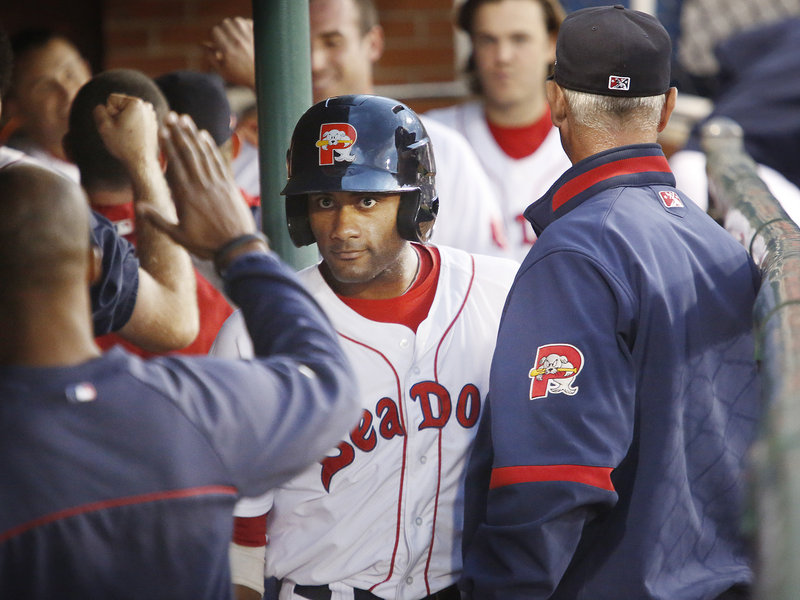 Tony Thomas of the Sea Dogs is congratulated in the dugout Friday night after scoring in the fourth inning of a 6-3 loss to the Akron Aeros.