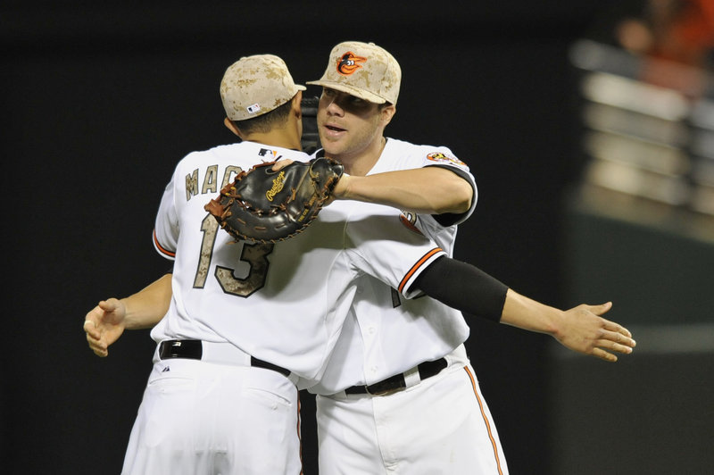 Baltimore infielders Chris Davis, right, and Manny Machado celebrate their 2-0 victory over Boston Friday night at Camden Yards, which moved the Orioles to within 1 1⁄2 games of the first-place Red Sox.