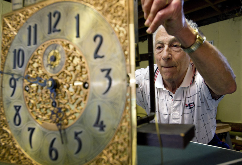 Jerry Fishman examines a valuable calendar clock in the basement workroom of his home in Stamford, Conn. Fishman, one of the last repairmen of his kind in Stamford, has retired after decades in the clock repair business.