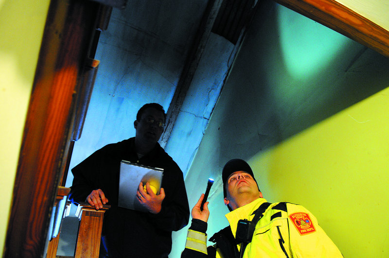 Augusta Code Enforcement Officer Robert Overton, left, and Augusta firefighter Arthur True inspect an apartment in the city. Several buildings throughout the city of Augusta have been cited for safety shortcomings.