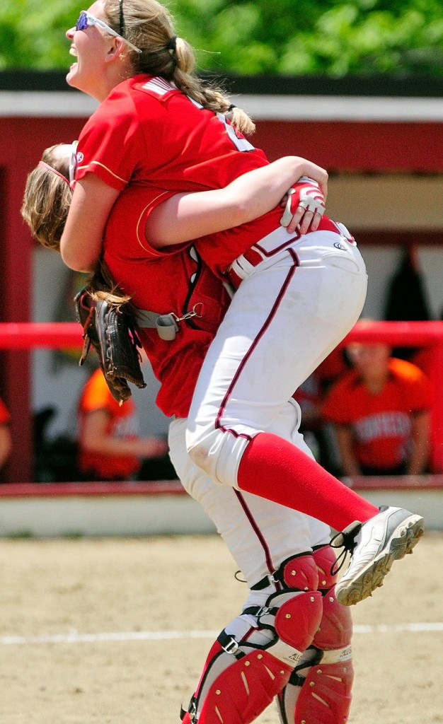 Alyssa Williamson receives a hug from catcher Megan Murrell after pitching Scarborough to the Class A state title, beating Skowhegan, 9-3.