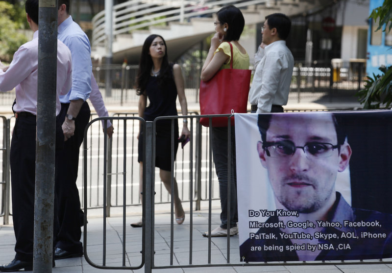 A banner supporting Edward Snowden, who leaked top-secret documents about sweeping U.S. surveillance programs, is displayed in Hong Kong's business district Wednesday. Snowden has also leaked information about British surveillance operations.