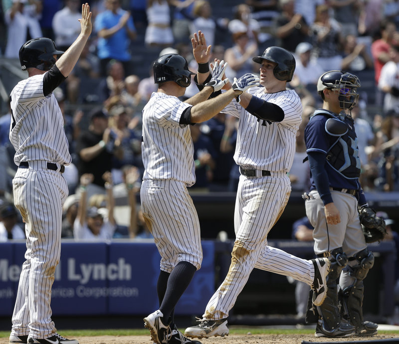 David Adams, right, celebrates with teammate Brett Gardner after scoring on a double by Vernon Wells during the Yankees' 7-5 win over Tampa Bay.