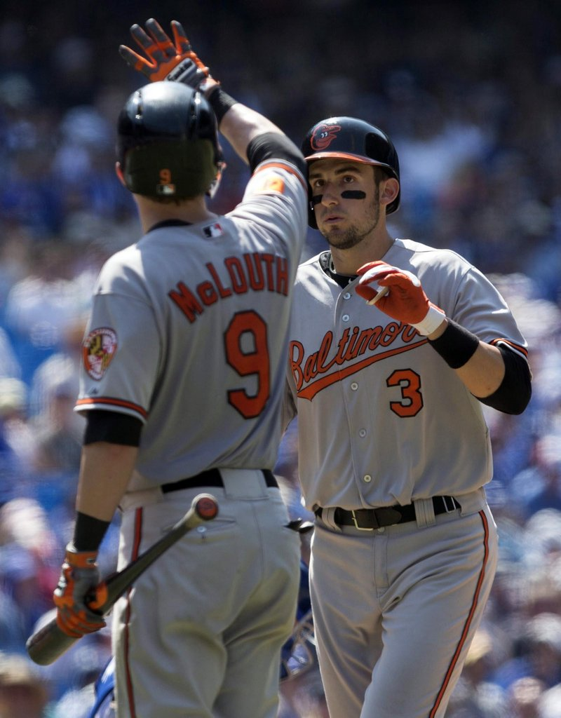 Ryan Flaherty is congratulated by Baltimore teammate Nate McLouth after hitting his second homer of the game in the ninth inning of a 13-5 loss to Toronto.
