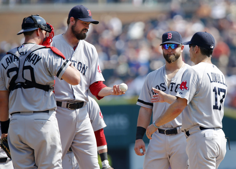 Red Sox reliever Andrew Miller, second from left, is pulled by bench coach Torey Lovullo (17) after loading the bases to start the eighth inning against the Tigers on Sunday. All three runners scored, helping Detroit take a 7-5 win.
