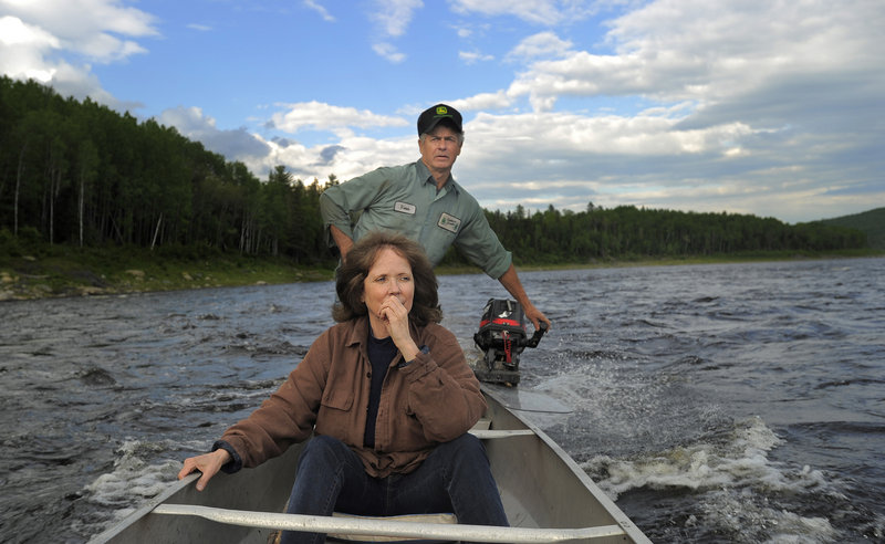 Cathie Pelletier rides on the St. John River in a canoe piloted by her brother, Vernon.