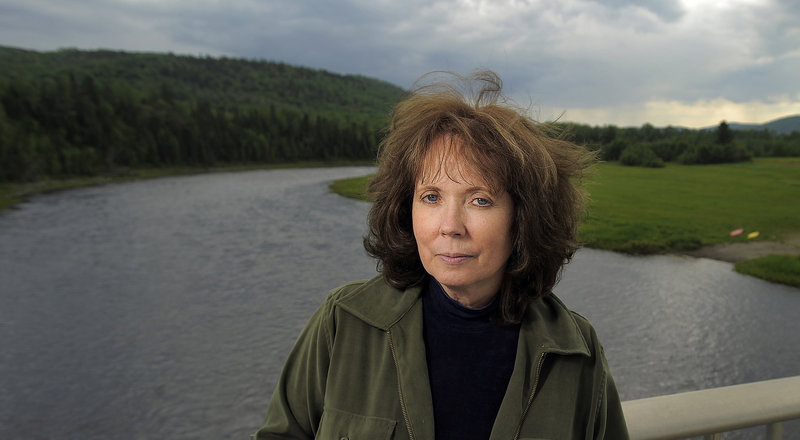 With the Allagash River in the background, Cathie Pelletier poses near her ancestral home in Allagash.