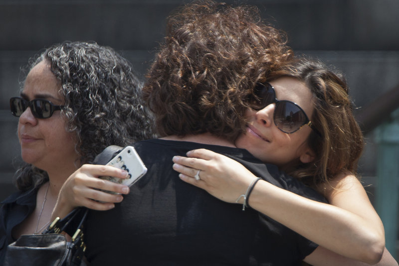 Actress Jamie-Lynn Sigler hugs a woman outside Cathedral Church of Saint John the Divine. Sigler played Gandolfini's daughter in the show.