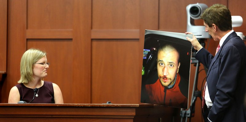 Mark O'Mara, George Zimmerman's attorney, shows a photo of Zimmerman taken the night that Trayvon Martin was fatally shot, to physician's assistant Lindzee Folgate during her testimony Friday in Sanford, Fla.