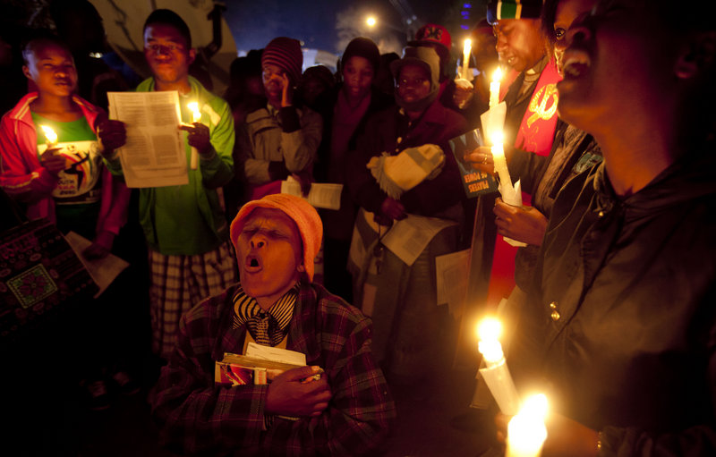 Well-wishers sing and pray for the health of Nelson Mandela, 94, on Friday night outside the hospital in Pretoria where former South African President Nelson Mandela is being treated. He was hospitalized June 8 for a recurring lung infection.