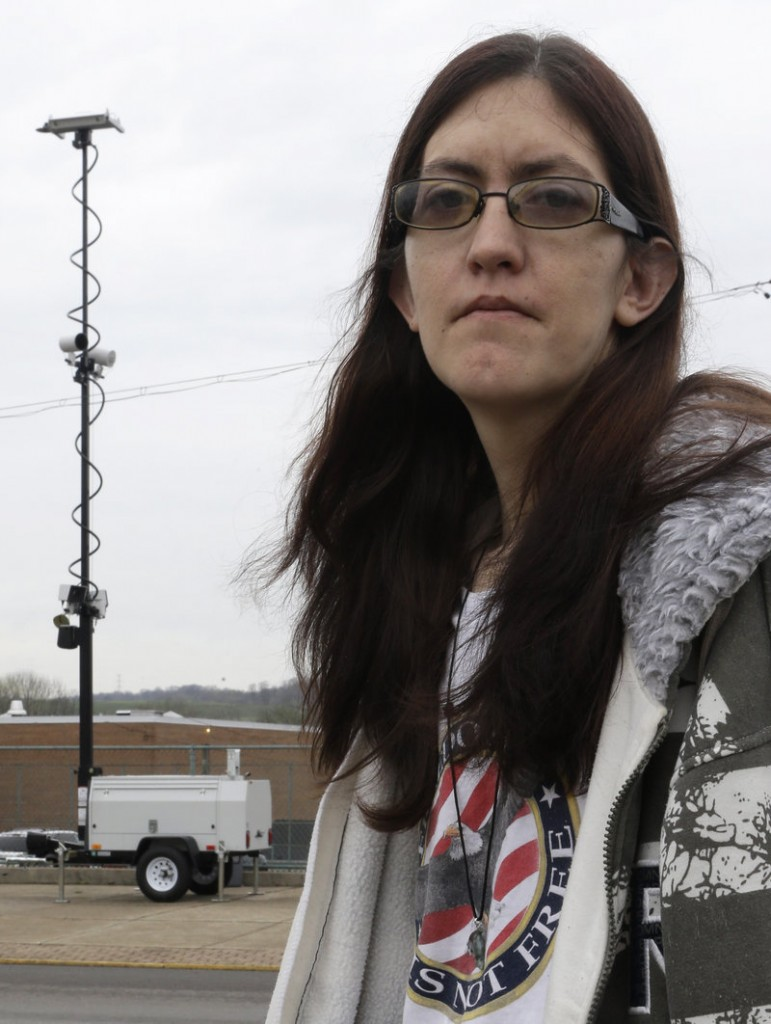 Holly Calhoun stands in front of a tower of speed cameras located near the Elmwood Quick Mart she manages in Elmwood Place, Ohio. Calhoun suspects government greed led to installation of the cameras in her village.