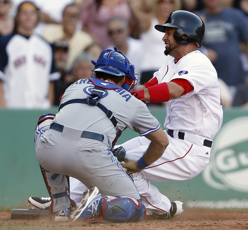 Boston's Shane Victorino is tagged out at home by catcher J.P. Arencibia after trying to score from second on a single by Dustin Pedroia during sixth-inning action of Saturday's game at Fenway Park.