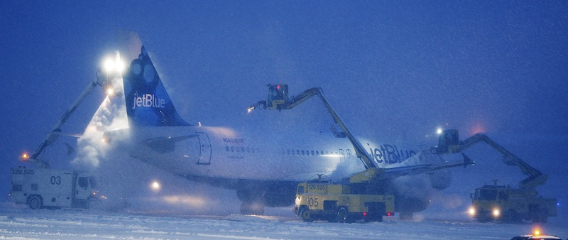 In this January 2012 file photo, a JetBlue plane gets de-iced prior to taking off at the Portland International Jetport. The city will receive $1.4 million for new snow-removal equipment from the FAA.