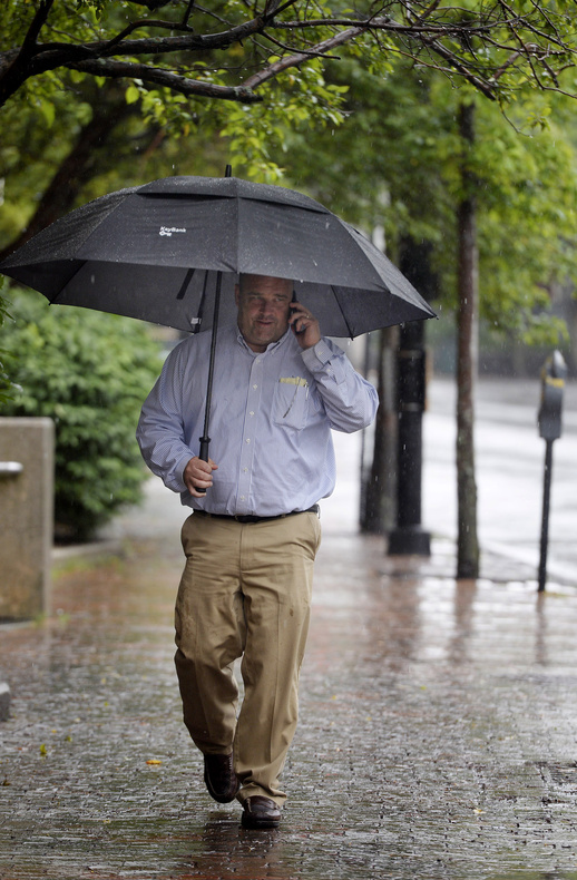Todd Zukowski of Portland takes cover under an umbrella while walking along Temple Street in Portland during Monday's rain.