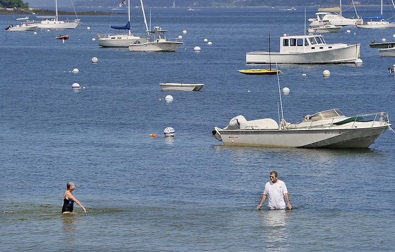 A couple enjoys the cool water off Falmouth's Town Landing near Casco Terrace Friday.
