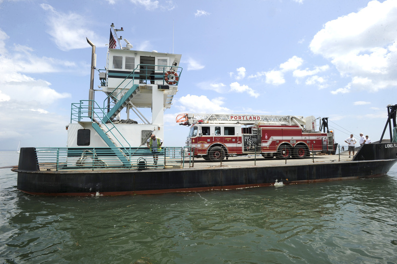 A barge leaves East End Beach in Portland on Wednesday carrying Portland Fire Department's Ladder 12, which has been refurbished and was on its way to Peaks Island.