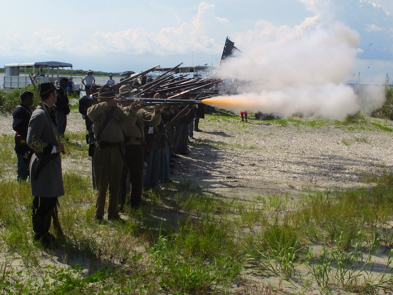 Re-enactors representing both North and South fire a volley on Morris Island near Charleston, S.C., on Thursday, July 18, 2013 during a observance of the 150th anniversary of the charge of the black 54th Massachusetts Volunteer Infantry in a fight commemorated in the film