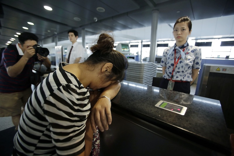 An unidentified family member of the two girls killed during the Asiana Airlines plane crash on Saturday, cries at the Asiana Airlines counter as she and other family members check infer the flight to San Francisco at the Pudong International Airport in Shanghai, China, Monday, July 8, 2013. The Asiana Airlines flight crashed while landing at San Francisco International Airport on Saturday, killing at least two people, injuring dozens of others and forcing passengers to jump down the emergency inflatable slides to safety as flames tore through the plane. The flight originated in Shanghai, China, and stopped over in Seoul, South Korea, before coming to San Francisco, airport officials said. (AP Photo/Eugene Hoshiko)