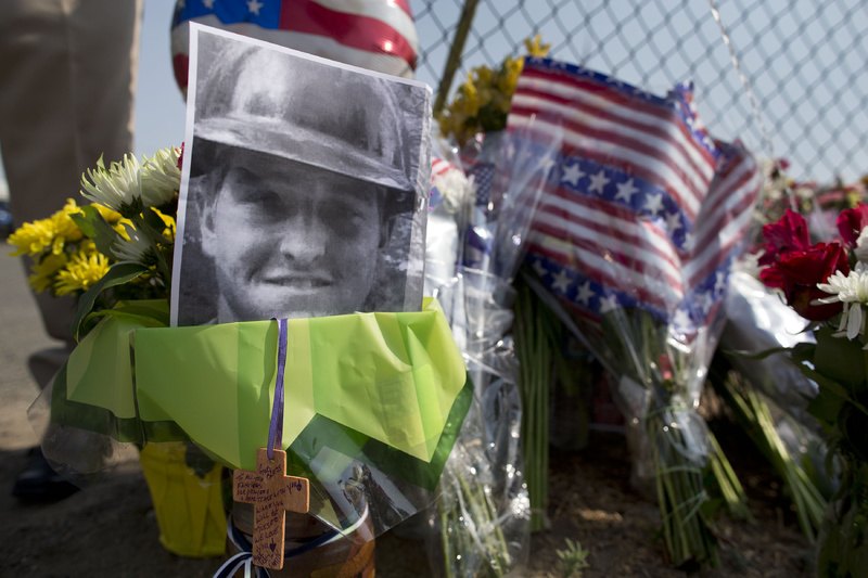 A photo of one of the 19 Granite Mountain Hotshot crew members who were killed fighting a wildfire near Yarnell, Ariz., on Sunday, sits at a makeshift memorial outside the crew's fire station on Monday in Prescott, Ariz.