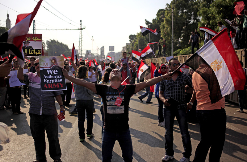 Opponents of Egypt's Islamist President Mohammed Morsi wave national flags during a protest outside the presidential palace in Cairo, Egypt, on Wednesday.