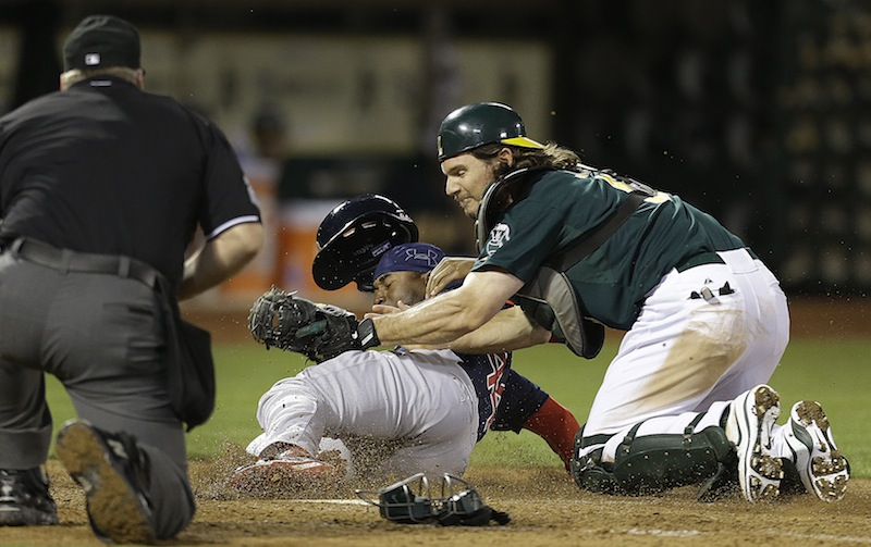 Boston Red Sox's Jackie Bradley Jr., center, is tagged out at home plate by Oakland Athletics catcher John Jaso in the ninth inning of a baseball game Friday, July 12, 2013, in Oakland, Calif. (AP Photo/Ben Margot)