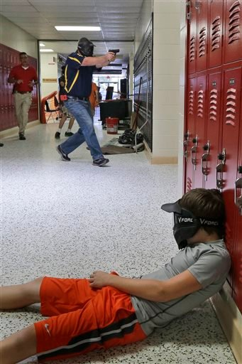 In this July 11, 2013, photo, a Clarksville schools faculty member, wearing a protective mask, rear center, carries a practice handgun toward a classroom in the city's high school, as students portray victims in a mock school shooting scenario.