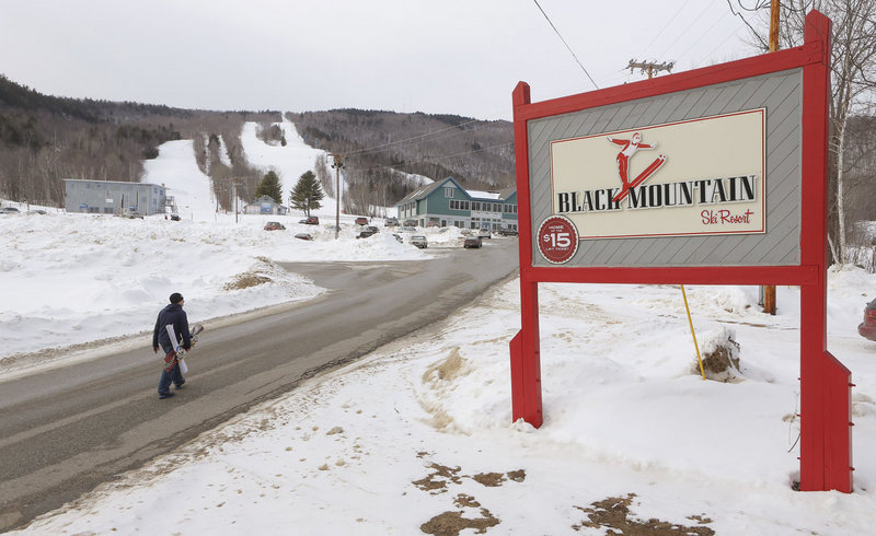 A snowboarder walks up the main access road to Black Mountain in Rumford in this January 11, 2013 file photo. The ski area will remain open after $125,000 was raised in three weeks.