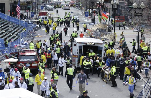 Medical workers aid injured people at the finish line of the Boston Marathon following explosions on April 15, 2013.