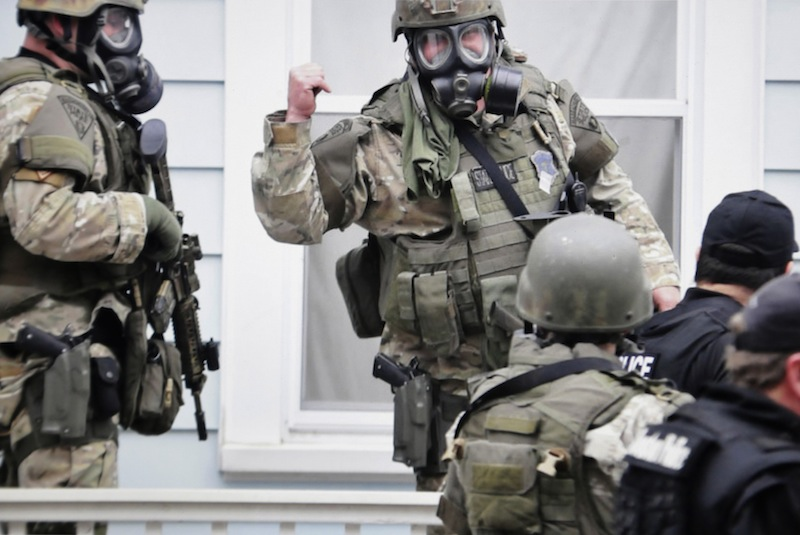 In this Friday, April 19, 2013 Massachusetts State Police photo, state troopers dressed in protective gear hold weapons as they stand near a home, in Watertown, Mass. Later that night, 19-year-old Boston Marathon bombing suspect Dzhokhar Tsarnaev was captured. (AP Photo/Massachusetts State Police, Sean Murphy)