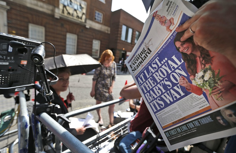 A news cameraman reads a newspaper across from St. Mary's Hospital's exclusive Lindo Wing in London, Monday, July 22, 2013. Buckingham Palace officials say Prince William's wife, Kate, has been admitted to the hospital in the early stages of labor. Royal officials said that Kate traveled by car to St. Mary's Hospital in central London. Kate _ also known as the Duchess of Cambridge _ is expected to give birth in the private Lindo Wing of the hospital, where Princess Diana gave birth to William and his younger brother, Prince Harry. The baby will be third in line for the British throne _ behind Prince Charles and William _ and is anticipated eventually to become king or queen. (AP Photo/Lefteris Pitarakis)