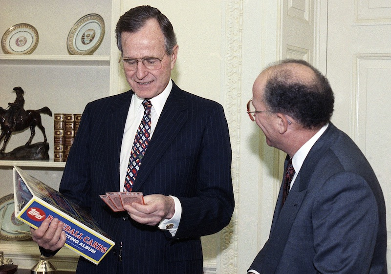 In this Feb. 5, 1990 file photo, President George H.W. Bush jokes with Arthur Shorin, President of Topps, Co., Inc., after Shorin presented him a book of baseball cards during a meeting in the Oval Office in Washington. Baseball cards depicting the former president as a Yale first baseman have fetched thousands of dollars each since they were specially-made for the White House in 1990. But Joe Orlando, president of Professional Sports Authenticator in Santa Ana, Calif., said Tuesday, July 9, 2013, thatmany of the Bush cards in circulation were not part of the set presented to the president.