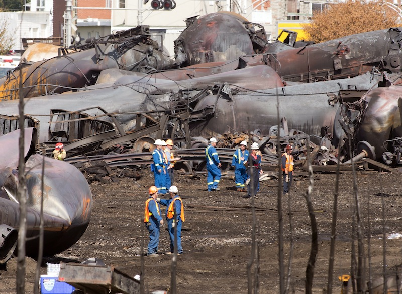 Workers stand before mangled tanker cars Tuesday, July 16, 2013, at the crash site of the train derailment and fire in Lac-Megantic, Quebec. The July 6, 2013, accident left 37 people confirmed dead and another 13 missing and presumed dead. (AP Photo/Ryan Remiorz, pool) Canada Quebec Montreal;transportation;business;Canada;Canadian;economic;economy;industry;move;ship;shipping;transit;transport;travel industry;commerce;tourism;fire;train;rail;derail;tragedy;disaster