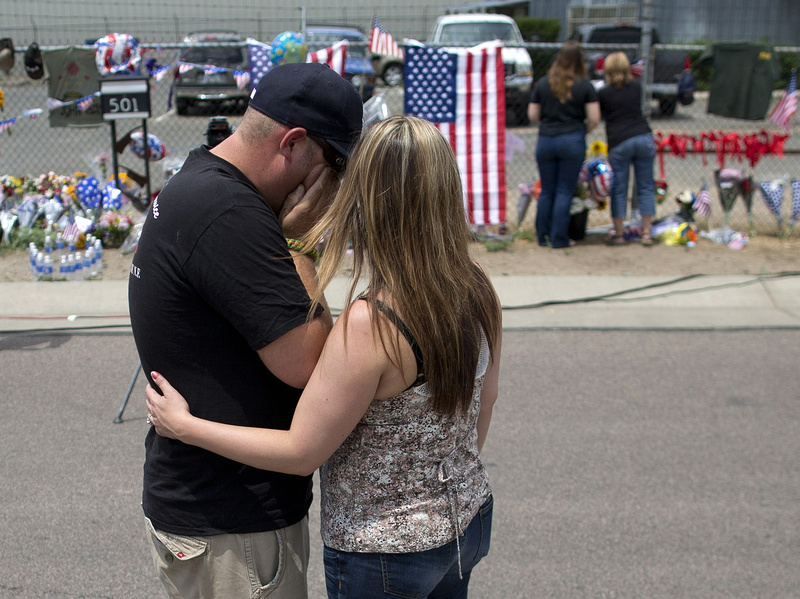 Joanne Barringer, right, comforts her husband Dave Barringer of Las Vegas after hanging a T-shirt on the fence outside the Granite Mountain fire station Monday in Prescott, Ariz. Barringer, who said he works as a firefighter for the U.S. Forest Service, said he was friends with many of the 19 Hotshots who were killed Sunday when an out-of-control blaze overtook the elite group near Yarnell, Ariz.