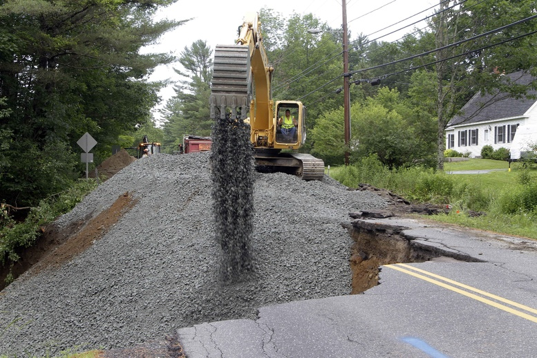 Kevin McNamara works to fill in a washed-out road Wednesday in Lebanon, N.H. Heavy rains caused flash flooding in the region.