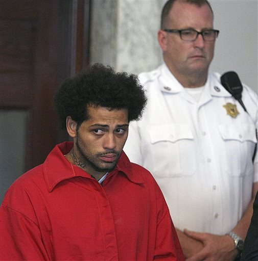Carlos Ortiz, left, stands in Attleboro District Court for his arraignment on weapons charges, Friday, June 28, 2013 in Attleboro, Mass. Ortiz was arrested Wednesday in Bristol, Conn., in connection with the murder case against former New England Patriots tight end Aaron Hernandez , now charged in the murder of Odin Lloyd. (AP Photo/The Boston Globe, George Rizer, Pool) carlos oritiz arraignment